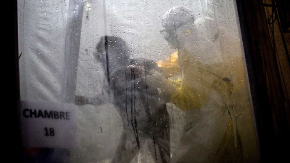 Health workers help an unconfirmed Ebola patient into her bed inside a treatment center in Democratic Republic of the Congo.