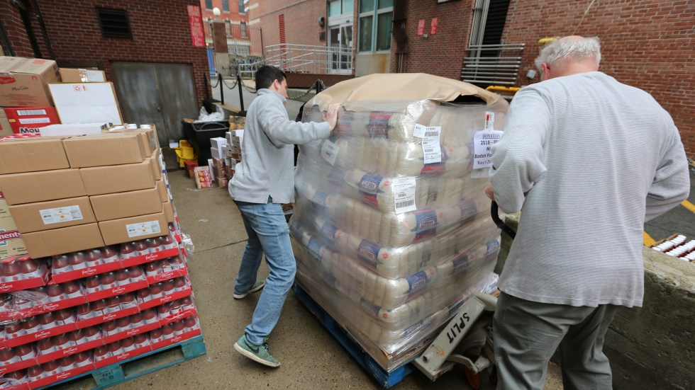 People gather items for a pop-up food pantry opened in Boston for men and women of the Coast Guard, the only branch of the armed services working without pay.