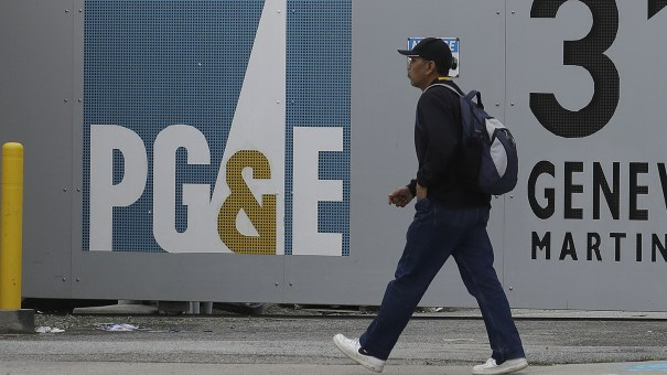 A man walks past a Pacific Gas & Electric Co. entrance in Daly City, Calif. After filing for bankruptcy last month, the company will replace half of its board of directors.
