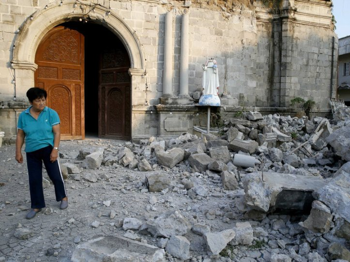A resident looks at the rubble of St. Catherine church on Tuesday, including the toppled head of a statue, following a 6.1 magnitude earthquake in Pampanga province northwest of Manila the previous day.Bullit Marquez/AP