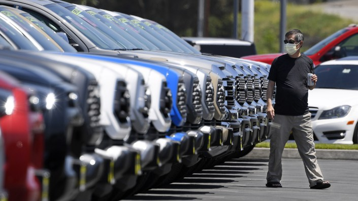 A customer looks at trucks at a Toyota dealership in El Monte, Calif., on Friday. Car sales have been recovering for several weeks, despite the continuing coronavirus outbreak.