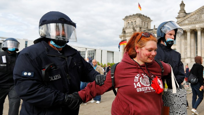 Police detain a demonstrator during a protest against the government