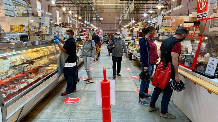 Shoppers wear masks at Eastern Market in Washington, D.C., on May 17. An NPR/PBS NewsHour/Marist poll finds that most Americans think it will take at least six months to return to normal daily life.
