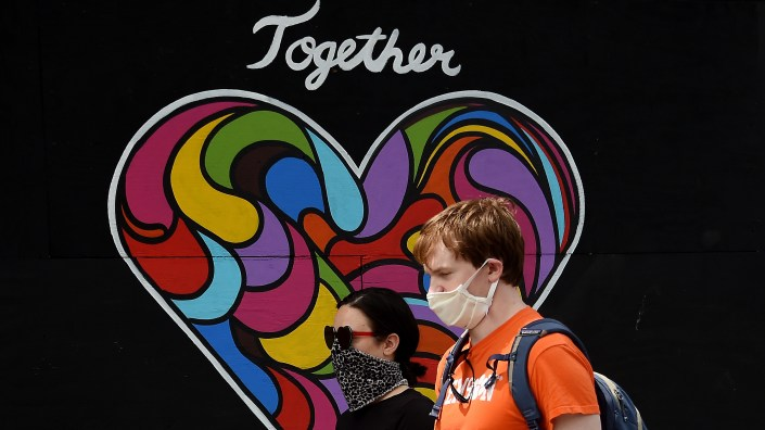 People wearing masks walk past a mural of encouragement displayed outside a store amid the coronavirus pandemic on Tuesday in Washington, D.C.