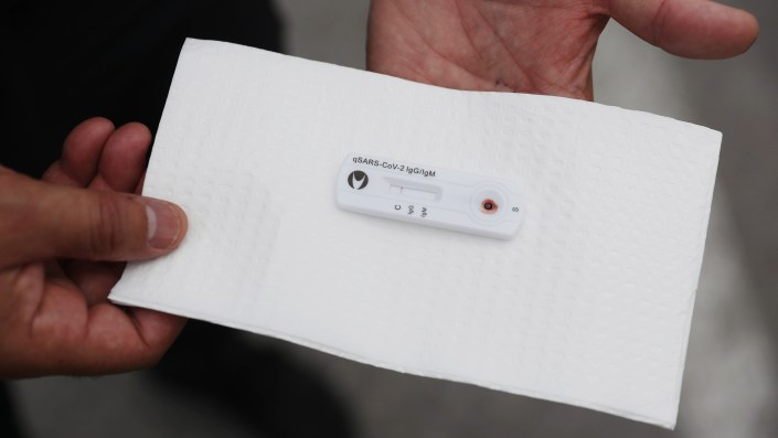 Anthony Reyes, police officer with the City of Miami, shows the results of his coronavirus antibody test at the Hard Rock Stadium testing site in Miami Gardens, Florida, Wednesday, May 06, 2020.