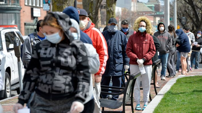 People wait in line to get food distributed by the National Guard in Chelsea, Mass., on April 16. Harvard researchers found areas with more poverty, people of color and crowded housing had higher mortality rates for the coronavirus.
