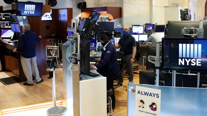 Traders wear masks as they work in their posts at the New York Stock Exchange Tuesday, the first day of in-person trading since the exchange closed in March due to the COVID-19 pandemic.