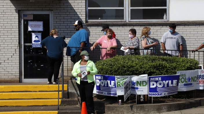 Voters stand in line as they wait their turn to cast their ballots during primary voting in Braddock, Pa., on Tuesday, June 2. Problems with absentee ballots and a smaller number of polling places led to long lines in several states as primary elections that were delayed by the coronavirus resumed.