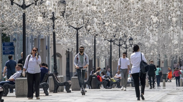 People enjoy warm weather in downtown Moscow on Monday. The mayor announced the gradual lifting of the coronavirus lockdown in the Russian capital.