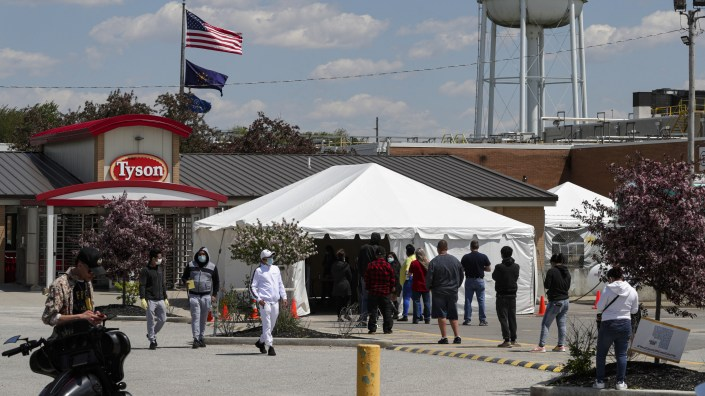 Workers line up to enter a Tyson Foods pork processing plant last month in Logansport, Ind. Some of the worst workplace coronavirus outbreaks have been in the meatpacking industry. Safety advocates say the companies still aren