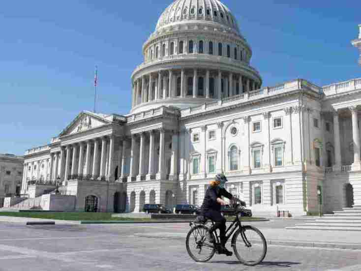 A woman wearing a mask to prevent the spread of the coronavirus rides a bike in front of the U.S. Capitol in Washington, D.C., on April 9.