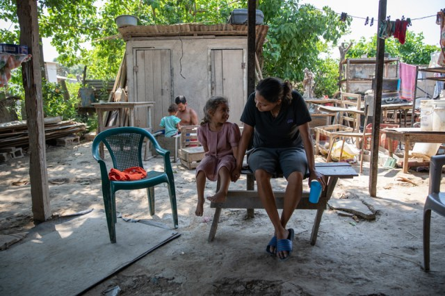 Glenda Ramos speaks with her niece, Allison, while her brother, Adan, builds furniture for the family in the back. The Ramos family lost everything after the hurricanes Eta and Iota swept through Northern Honduras in late 2020.