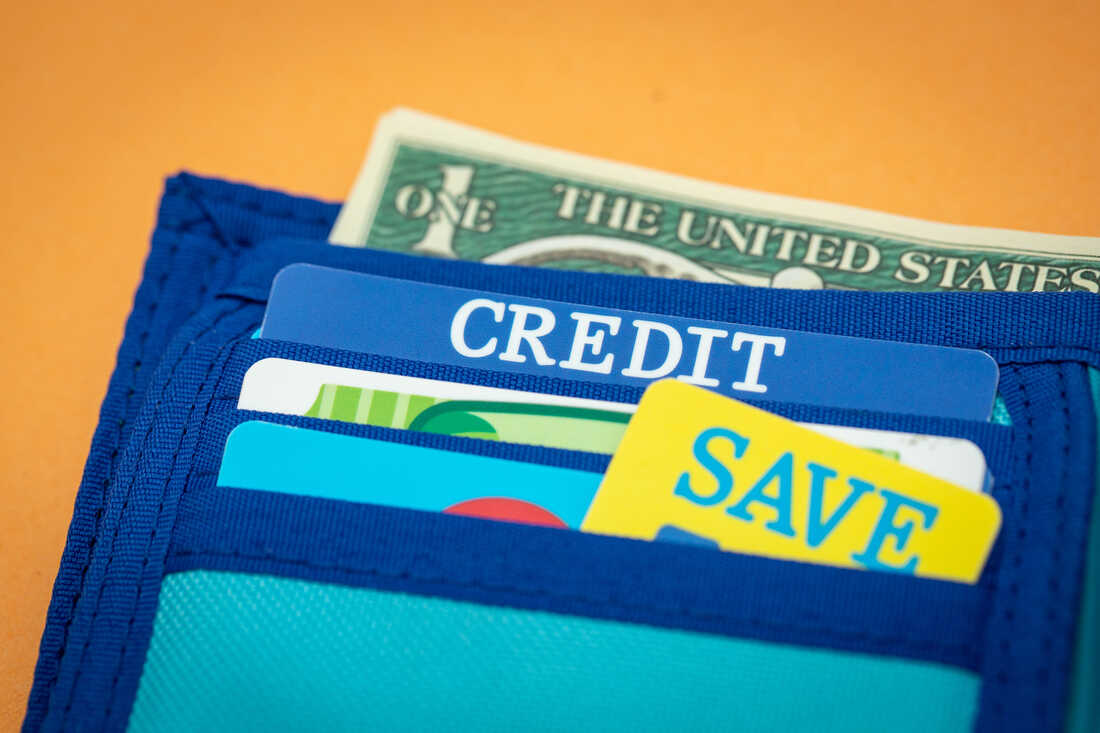 A close-up of a toy wallet full of toy money, toy coupons and fake cards, including a fake credit card, photographed against an orange backdrop.