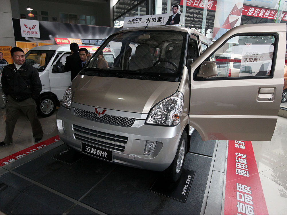 Visitors look at minivans at a GM joint venture dealership in China.