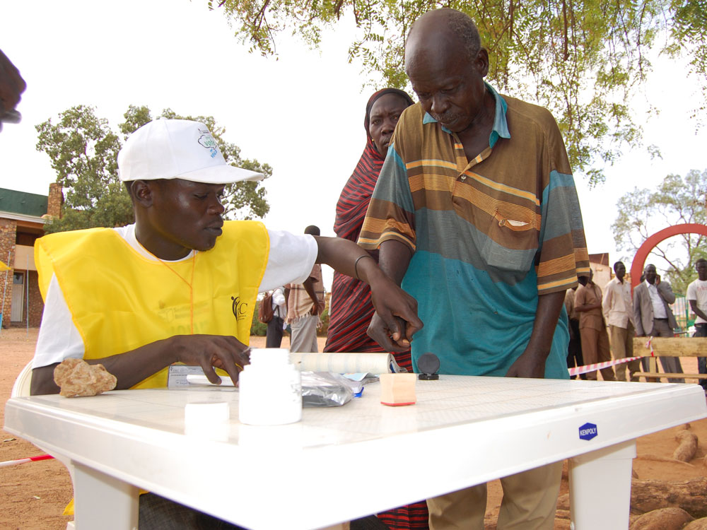 Poll worker helps prospective voter register for next month's referendum on independence for Southern Sudan