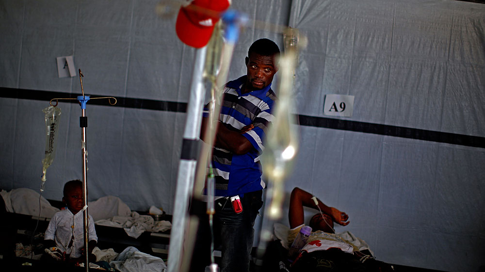A man looks over a room of cholera victims in Port au Prince, Haiti