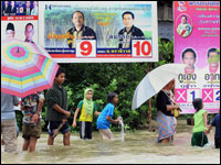 Children play in flood water next to election campaign billboards