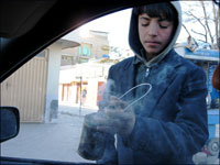 Fahim, 11, waves his can of burning incense inside a car on a busy Kabul street.