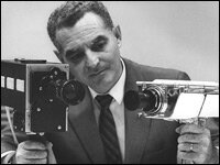 Stan Lebar holds the two cameras he helped design for the Apollo 11 mission.