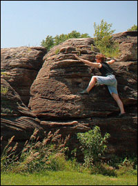 Kij Johnson climbing a large rock.