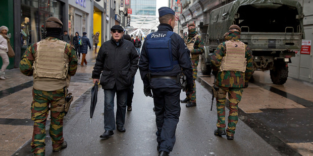 Belgian Army soldiers and police patrol an otherwise busy shopping street in Brussels. Photo / AP