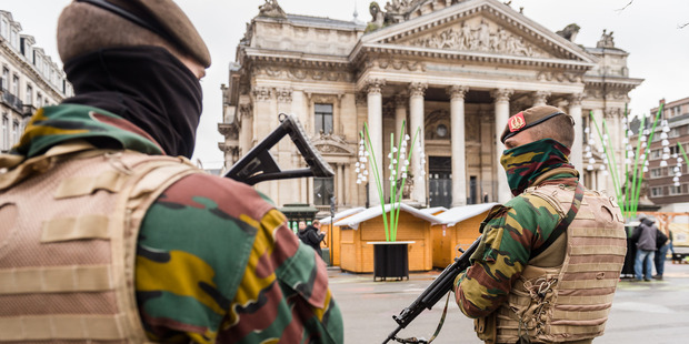 Belgian Army soldiers patrol near Christmas huts in front of the old Brussels' stock exchange. Photo / AP