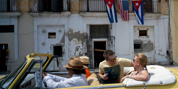 Tourists ride in a classic American car past a balcony decorated with Cuban and U.S. flags in Havana, Cuba. Photo / AP
