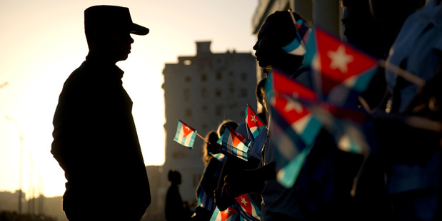 A soldier is silhouetted against the early morning sky as people holding Cuban flags wait for the motorcade transporting the remains of Cuban leader Fidel Castro in Havana, Cuba. Photo / AP
