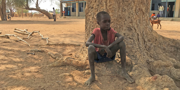 Thor Athiam, 9, sits outside of a classroom waiting under a tree in South Sudan. Famine has been declared in two counties. Photo / AP