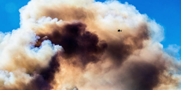 Fire fighters and helicopters fight the blaze on the Port Hills Christchurch. Photo / Martin Hunter - Christchurch Star