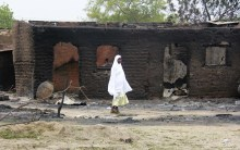 A woman walks past burnt houses in the aftermath of what Nigerian authorities said was heavy fighting between security forces and Islamist militants in Baga, a fishing town on the shores of Lake Chad, adjacent to the Chadian border, April 21, 2013. The bloody gun battle against Islamist insurgents in Nigeria last week involved forces from neighbouring Chad and Niger, officials said on Tuesday, as West African countries increasingly view jihadist groups as a cross-border threat. There was no confirmation of the death toll from Friday's fighting, but a Nigerian military source said dozens may have died, many of them civilians. The Nigerian Red Cross said it was checking reports from locals that 187 people had died, but had still not obtained security clearance to go into Baga. Picture taken April 21, 2013.   REUTERS/Stringer (NIGERIA - Tags: CIVIL UNREST POLITICS) - RTXZ0PR