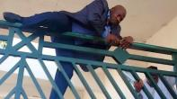 Hon Kawu Sumaila, dep minority leader of the House of Reps, climbing NASS gate to have access to the premises.