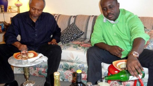 Pius Adesanmi and Okey Ndibe. Pius serving himself palm wine wile Okey enjoys swallow.