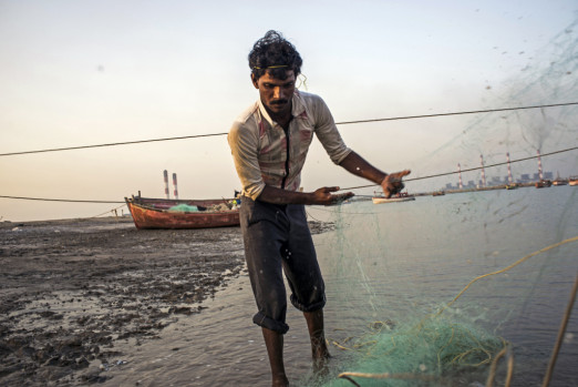 A fisherman near Mundra, India, prepares the net for the next day's fishing trip. Locals say a World Bank Group-backed project in the area has depleted fish stocks. Sami Siva / International Consortium of Investigative Journalists