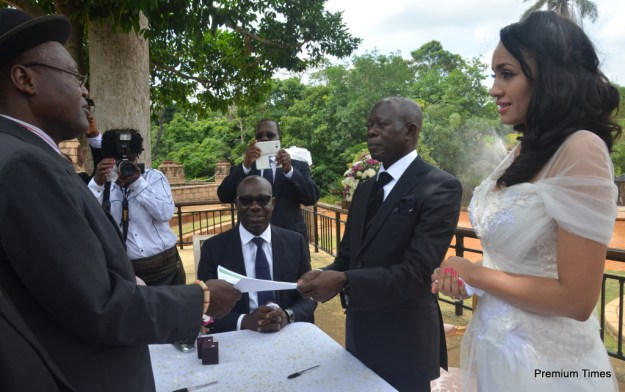 The officiating minister hands the marriage certificate to the Comrade Governor.