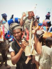 A young boy with a snake wrapped across his shoulders