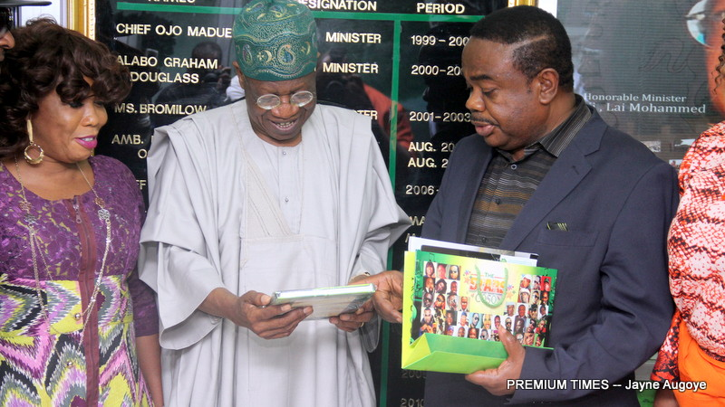 Minister of Communication, Lai Mohammed receiving a copy of a book from COSON Chairman, Tony Okoroji, as popular gospel singer, Kenny Saint Best, looks on during a courtesy visit to the Minister in Abuja on Thursday, November 24, 2016.