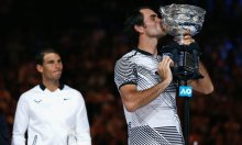 Roger Federer kisses the trophy after winning his Men's singles final match against Rafael Nadal. Photograph: Issei Kato/Reuters