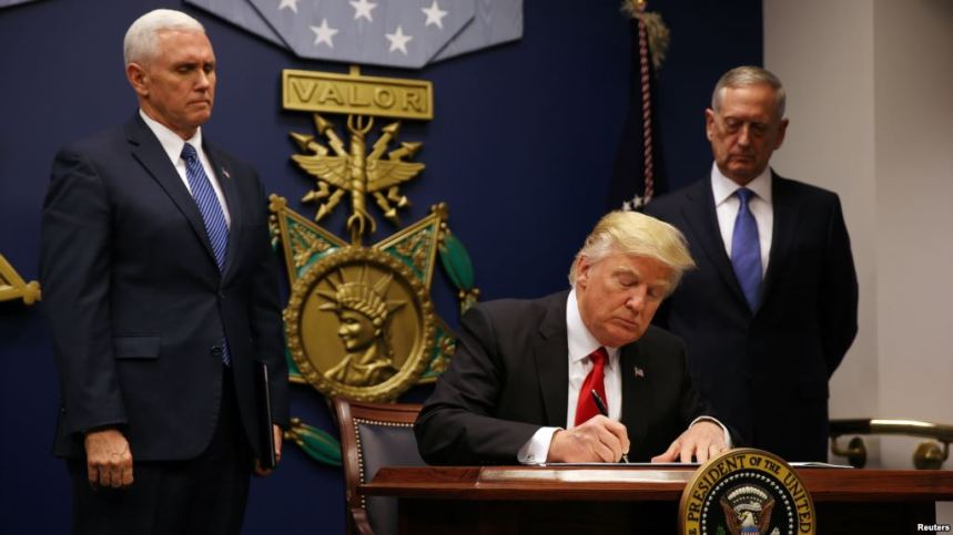 President Donald Trump, signing new executive order [Photo: voanews.com]