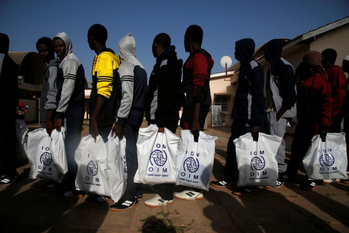 Gambian migrants deported from Libya stand in line with plastic bag from the International Organization for Migration (IOM) as they wait for registration at the airport in Banjul, Gambia April 4, 2017. REUTERS/Luc Gnago