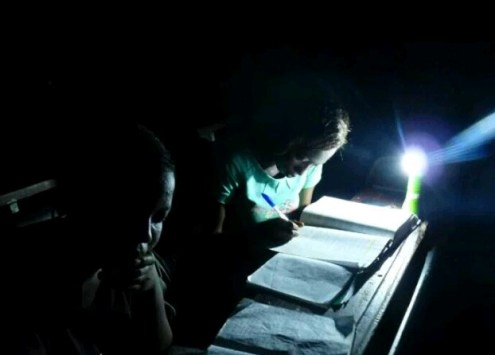 Students preparing for exams in darkness