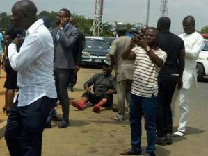 Senator Dino Melaye, sitting on the floor after jumping out of a moving police van