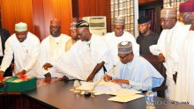 President Muhammadu Buhari signing the 2018 Appropriation Bill into law at the Presidential Villa in Abuja on Wednesday (20/6/18). Standing behind him are: Senior Special Assistant to the President on National Assembly Matter (House) Suleiman Kawu; Representative of the Senate President, Sen Ibn Na'ala; Chairman, House of Representatives Committee on Appropriation, Rep. Mustapha Bala; Senior Special Assistant to the President on National Assembly Matter (Senate) Sen Ita Enang; Chairman, Senate Committee on Appropriation, Sen Danjuma Goje; Vice President Yemi Osinbajo; Representative of Speaker, House of Representatives, Rep Ado Doguwa and Chief of Staff, Alhaji Abba Kyari; 03269/20/6/2018/Callistus Ewelike/NAN