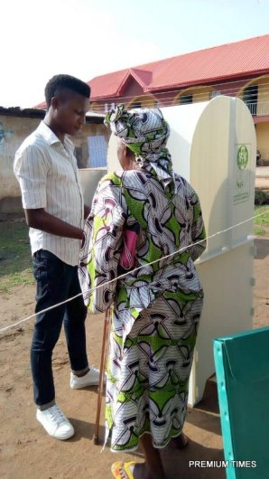 "Old woman assisted by her ""son"" at PU 15 ward 9, Emure"
