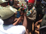 Governor Umahi being decorated with a galarnd of honour by Miss NYSC Batch B stream 1.
