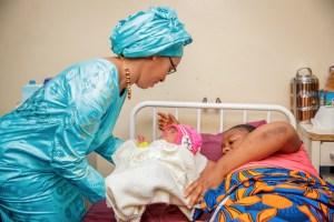 Mrs. Barrow cuddling a baby at the post natal ward