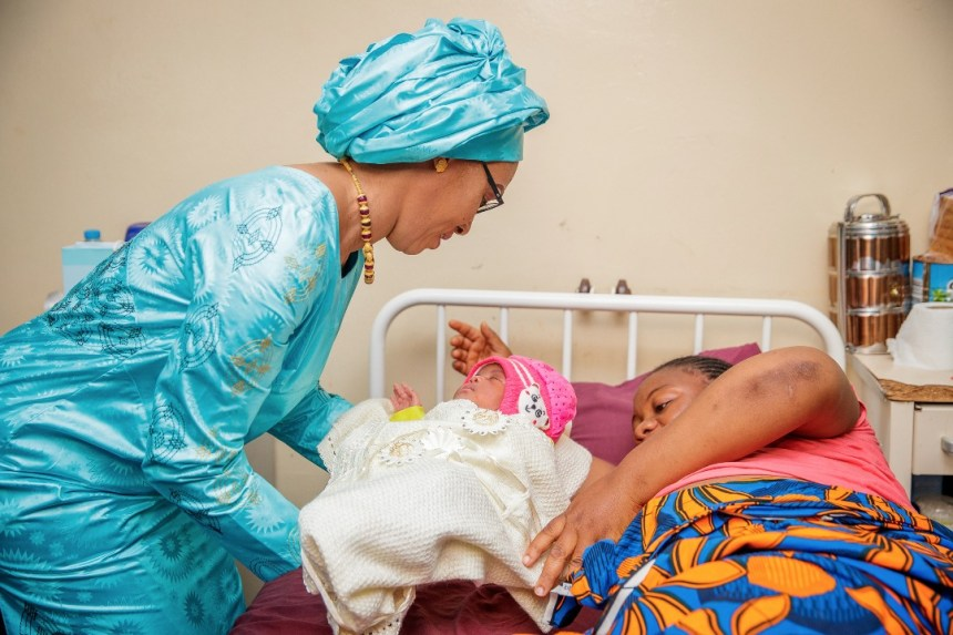 Mrs. Barrow cuddling a baby at the post natal ward