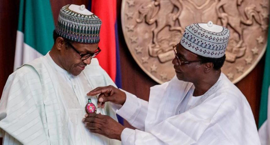 Chairman, Nigerian Legion, retired Brig.-Gen. Adakole Akpa decorating President Muhammadu Buhari with the 2019 Armed Forces Remembrance Day Emblem during the launch of the Appeal Fund at the Presidential Villa in Abuja on Wednesday