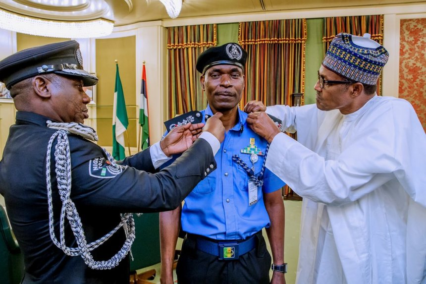 Acting IGP Mohammed Adamu being decorated by President Muhammadu Buhari and outgoing IGP, Ibrahim Idris