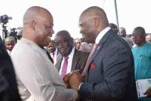 Senator Godswill Akpabio and Governor Udom Emmanuel holding hands during a rare encounter at Catholic Church, Uyo
